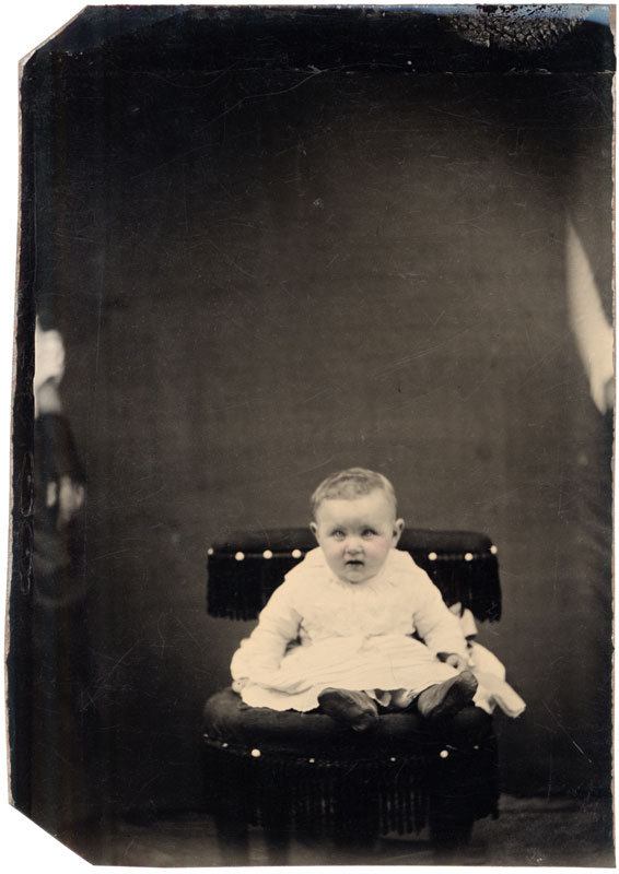 Tintype of a young child sitting precariously on a studio chair