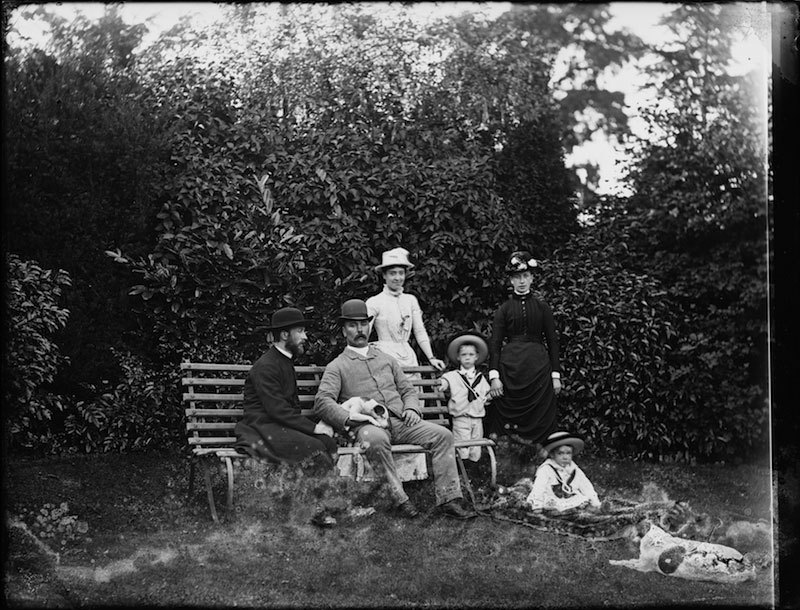 Glass negatives of a group of people in a garden